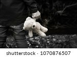 Stock photo black and white photo of kid holding teddy waking alone in the forest rear view of a boy standing 1070876507
