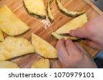 cutting pineapple on wooden...   Shutterstock . vector #1070979101