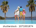 Family with two children standing  on the beach on sea coast