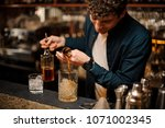 young barman pouring a sweet... | Shutterstock . vector #1071002345