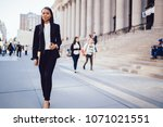 Small photo of Full length portrait of successful african american student of faculty of law strolling with folder in hand near university.Positive female employee with dark skin in formal wear walking outdoors