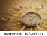 Small photo of Kitchen, a metal clock on the wall, the arrows show noon. Meals, lunch, diet. Light golden background, bottom view, vignetting. The product of mass production.