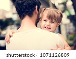 dad carrying his daughter with... | Shutterstock . vector #1071126809