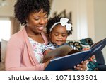 mother reading a book to her... | Shutterstock . vector #1071133301