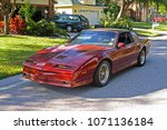 Small photo of SARASOTA, FLORIDA/USA - OCTOBER 18, 2007: A Flame Red Metallic 1988 Pontiac Trans AM GTA parked in a residential neighborhood.