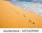 beach  wave and footprints at... | Shutterstock . vector #1071229565