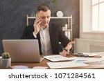 serious male financial advisor... | Shutterstock . vector #1071284561