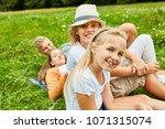 blond girl and her family relax ... | Shutterstock . vector #1071315074