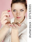 Young woman looking at pills in hand - stock photo