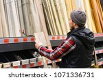 a young man chooses baseboard... | Shutterstock . vector #1071336731