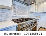 Stock photo white kitchen with stainless steel hood over gas cooktop and carrera marble backsplash 1071365621