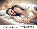 happy young couple in bed.... | Shutterstock . vector #1071420731