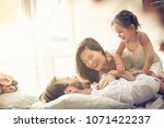 happy family playing in bed.... | Shutterstock . vector #1071422237