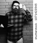 Small photo of Bearded man, long beard. Brutal caucasian unshaven hipster holding laptop with mag or cup in red black checkered shirt with hat and glasses on brown brick wall studio background