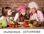 granny with two granddaughters... | Shutterstock . vector #1071495485