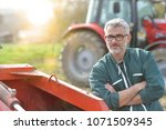 farmer standing by tractor...   Shutterstock . vector #1071509345