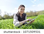 agronomist in crop field using... | Shutterstock . vector #1071509531
