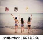 three women on the beach are... | Shutterstock . vector #1071522731