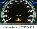 Small photo of Fuel Low warning on gauge display with red light icon alert sign showing oil or gas almost empty and cars or automobile vehicle need energy refill for road trip travel