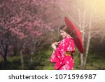asia woman with kimono and red... | Shutterstock . vector #1071596987