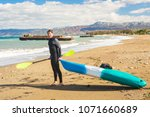 man carrying kayak at sea beach | Shutterstock . vector #1071660689