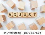 Small photo of ADJUST word on wooden cubes
