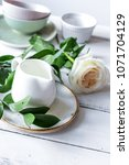 Small photo of ceramic tableware with flowers on white background