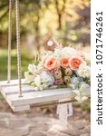 Small photo of Wedding flowery bouquet of pastel flowers on a wooden swing