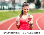 sporty woman using smartphone...   Shutterstock . vector #1071884855