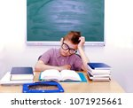 young schoolboy sitting writing ... | Shutterstock . vector #1071925661