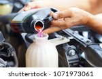 male hand filling car cooling... | Shutterstock . vector #1071973061