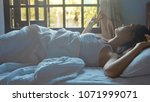 Small photo of Young woman sleeping in bed at home and gradually waking up at morning. Female waking up and looks out of window.
