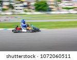 Small photo of Go Kart Racer on track, Shot is panned to emphasize speed.
