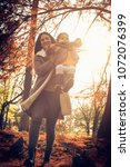 mother carrying her daughter in ... | Shutterstock . vector #1072076399