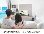 happy family watches television ... | Shutterstock . vector #1072128434