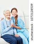 Small photo of Smiling nurse on home care makes home visit to happy senior citizen