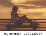 silhoutte of a girl while... | Shutterstock . vector #1072130399