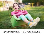 little girl swinging at... | Shutterstock . vector #1072163651