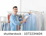 young man steaming shirt at dry ... | Shutterstock . vector #1072234604