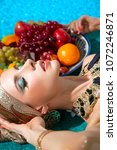 girl with a plate of fruit lies ... | Shutterstock . vector #1072246871