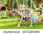 young friends having barbecue... | Shutterstock . vector #1072283384