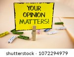 Small photo of Writing note showing Your Opinion Matters Motivational Call. Business photo showcasing Client Feedback Reviews are important written Yellow Sticky Note Paper on plain background Wooden Clips.