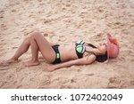woman wearing beach hat is... | Shutterstock . vector #1072402049
