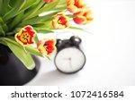 tulips and black alarm clock.... | Shutterstock . vector #1072416584