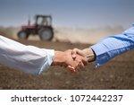 two businessmen shaking hands... | Shutterstock . vector #1072442237