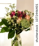 Small photo of Close-up of beautiful bridal bouquet sitting in a vintage jar on a white table and aery atmosphere