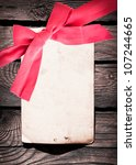 Red bow with card on old wood background - stock photo