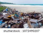 pollution on the beach of... | Shutterstock . vector #1072490207