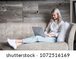 young woman sitting with laptop | Shutterstock . vector #1072516169