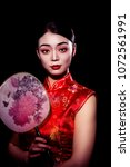 Small photo of beautiful Chinese girl in red traditional with gold embroidery robe on black background